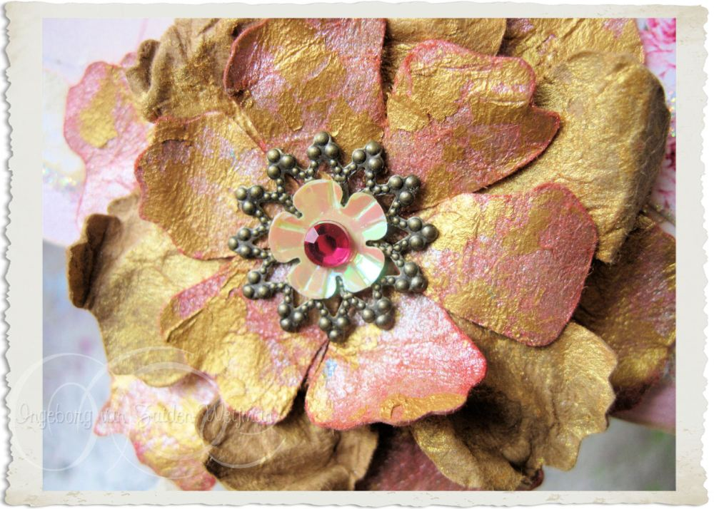 Details of handmade gold pink paper flower with bronze heart and sequins