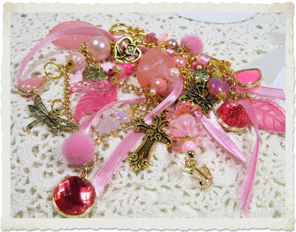 Pink gold brooch with golden charms and bling