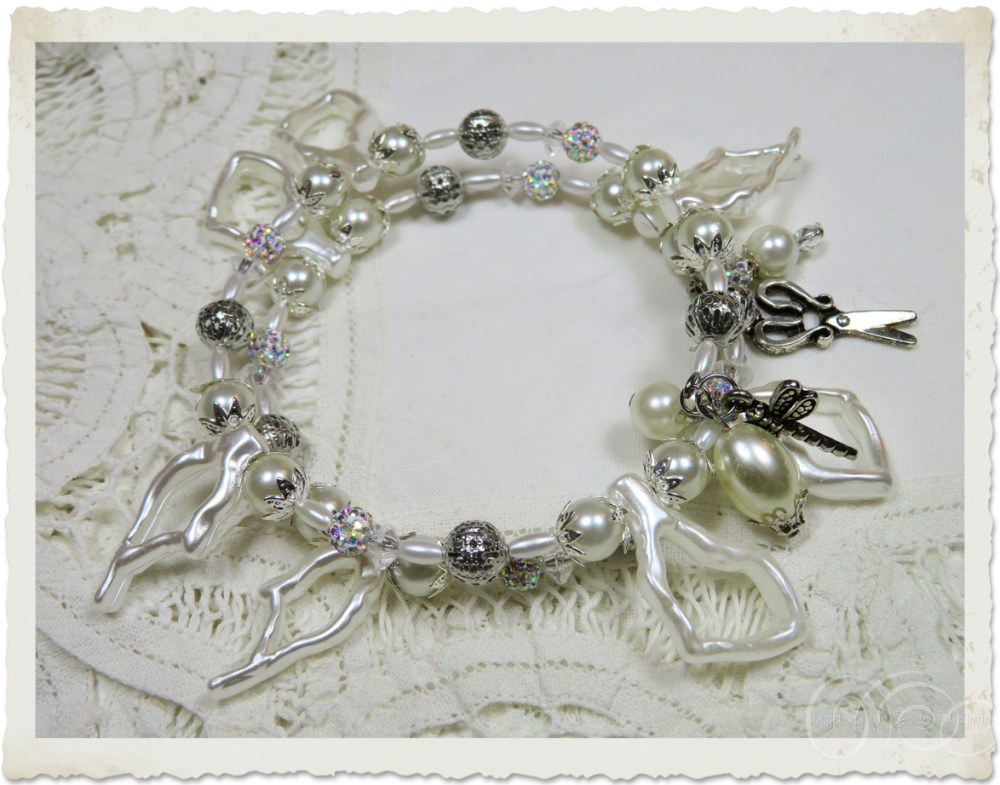 Handmade white pearl memory wire bracelet with silver dangles and accents