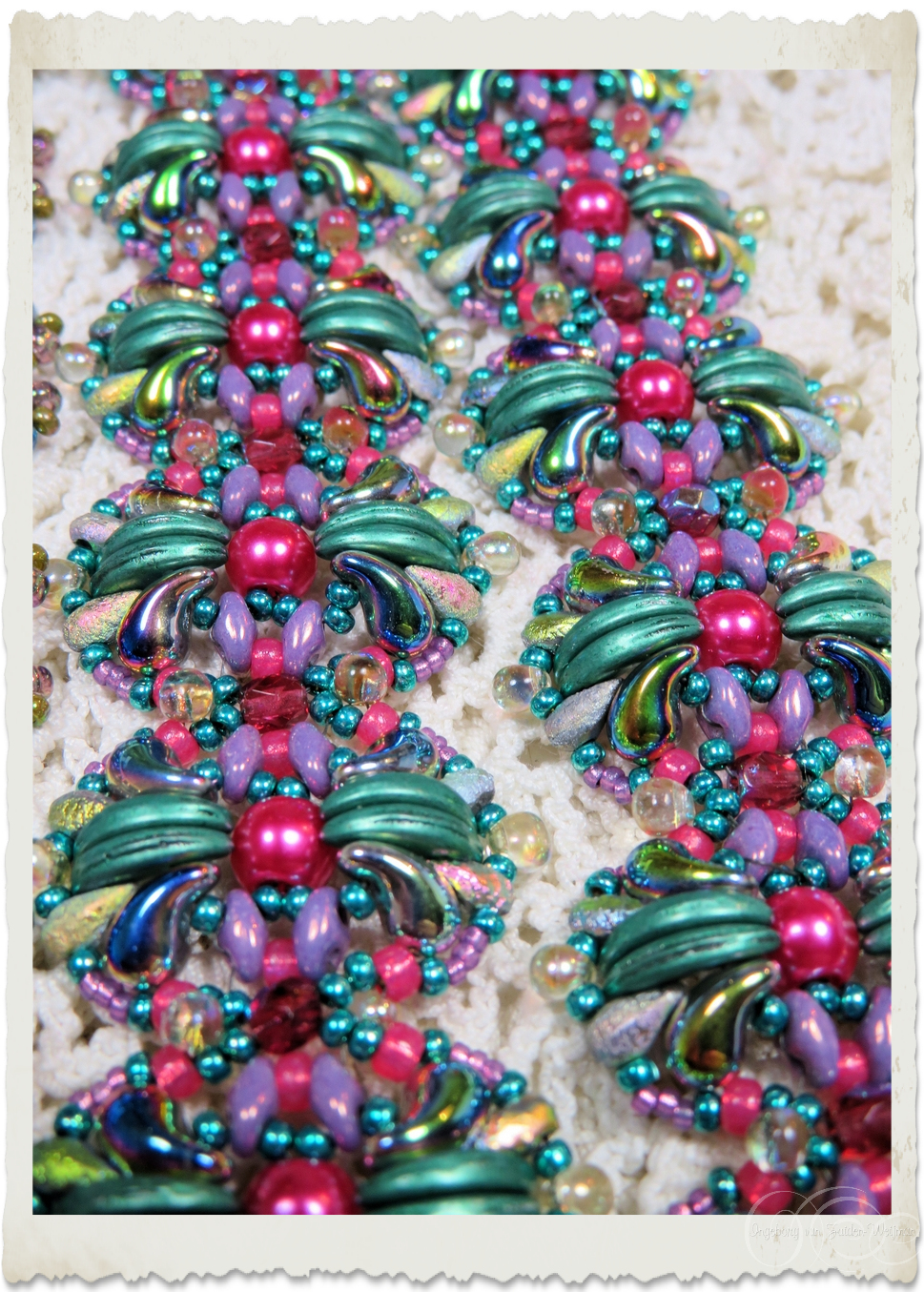 Details of pink pearls and blue green crescent beads.