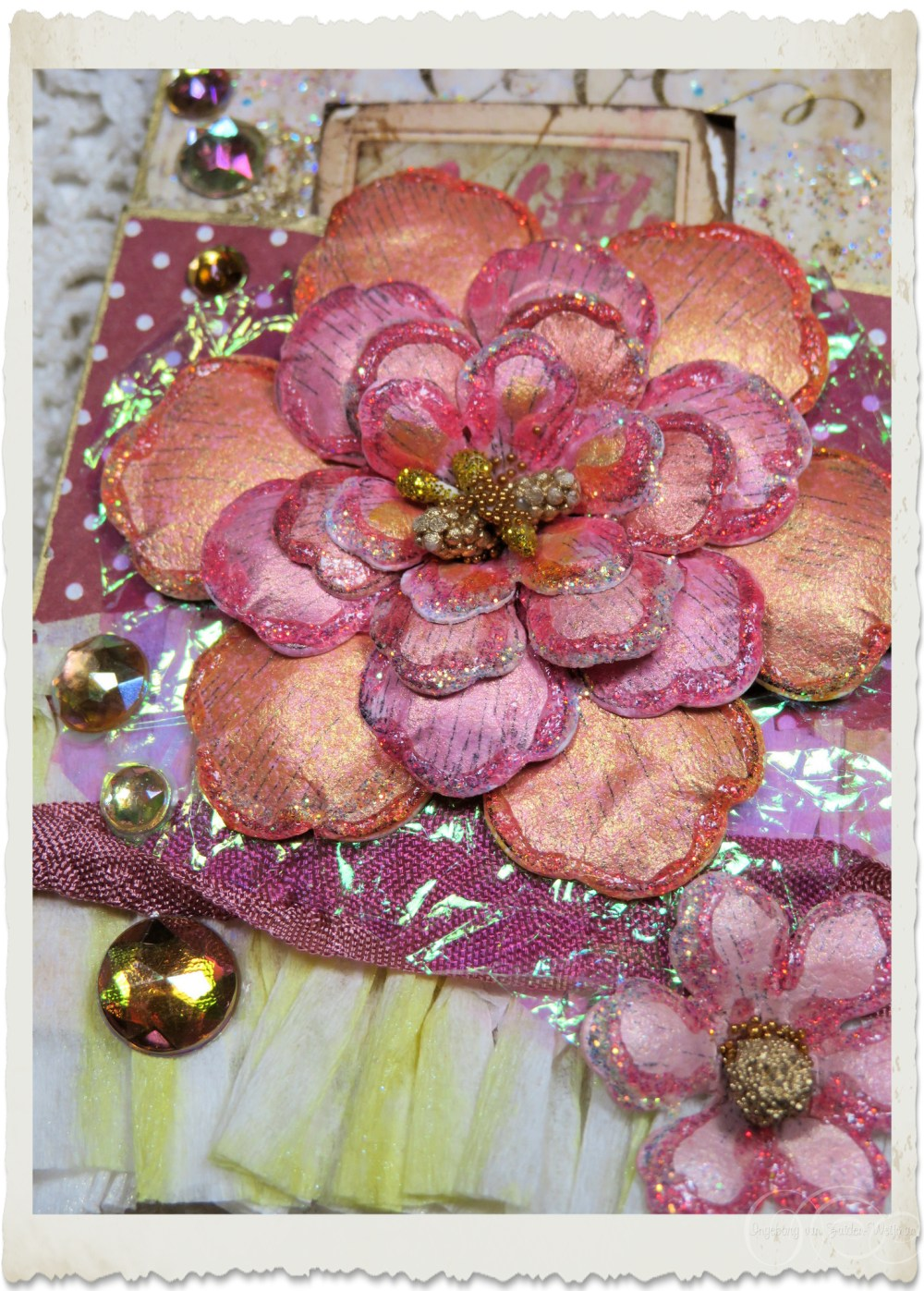 Handmade glitter flower with golden accents on iridescent paper