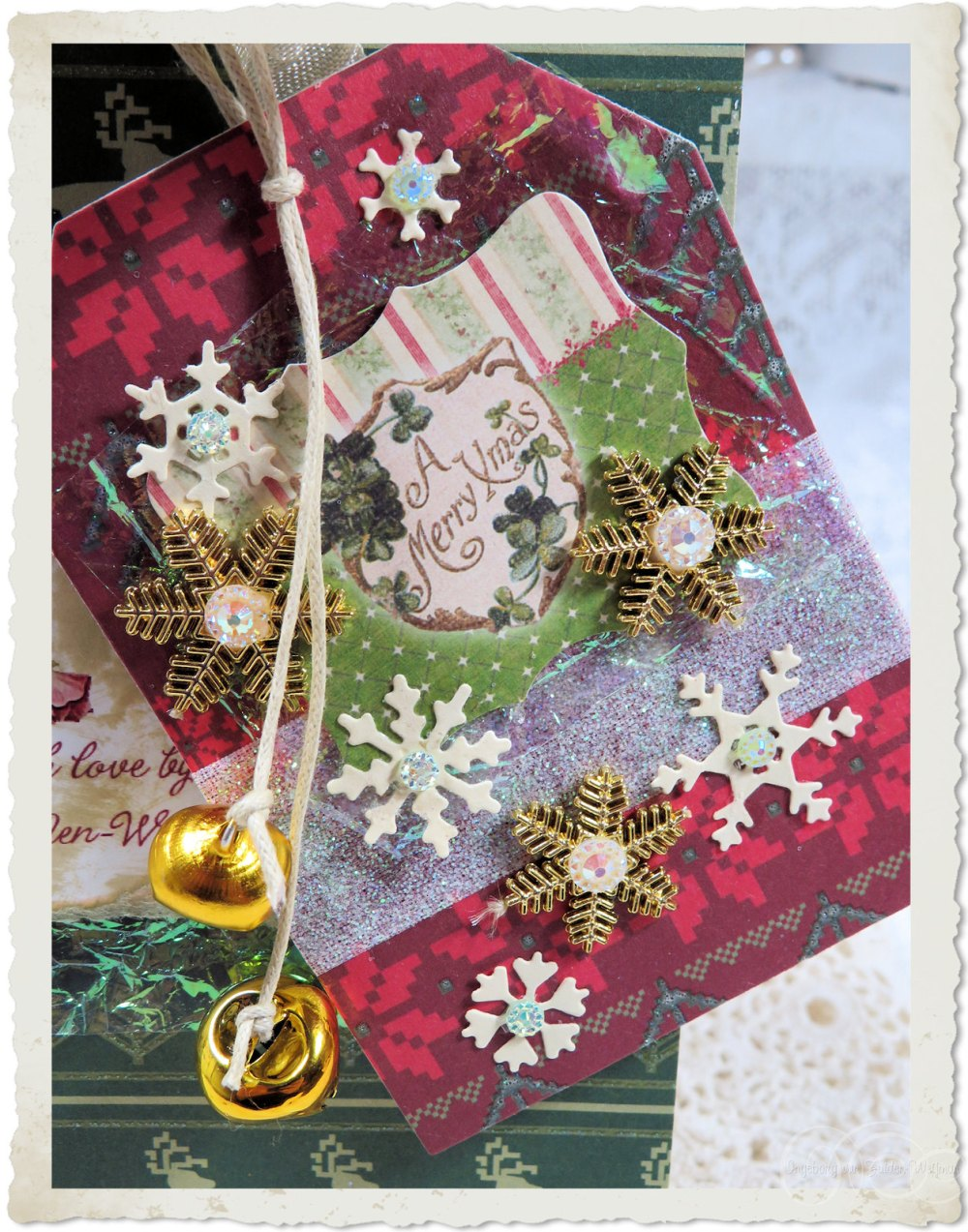 Handmade Christmas paper tag with golden bells and snowflakes
