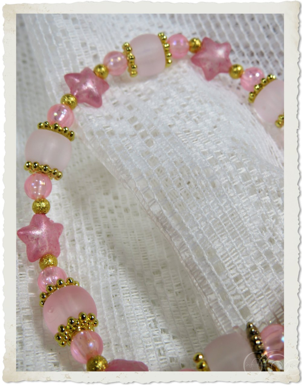 Details of pink star beads and golden spacers