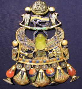 The central yellow scarab beetle in Tutankhamun's pectoral. The beetle is carved from Libyan desert glass, formed when a meteorite struck the sands of the desert.