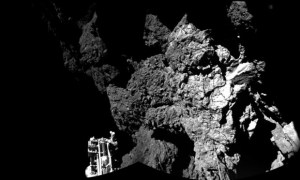 The fiorst image sent back by Philae from the surface of the comet. The lander's leg is in the bottom right corner.