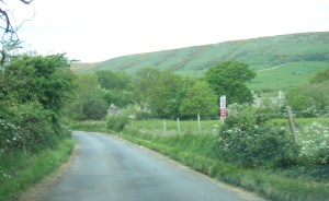 The approach to the village. Army 'keep out' sign to the right of the road.