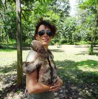 turista con in braccio un bradipo