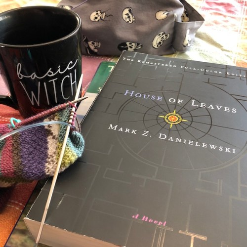 A still life, featuring a cup of tea in a Basic Witch mug, a knit sock, and a couple of books. House of Leaves is the title on top.