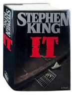Book cover: It by Stephen King. A paper boat floats dangerously close to a sewer drain.