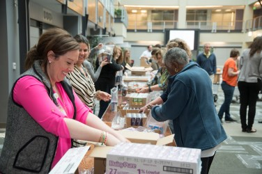 Volunteers pack food bags for the Backpack program in Biotech Atrium, Innovation Quarter.