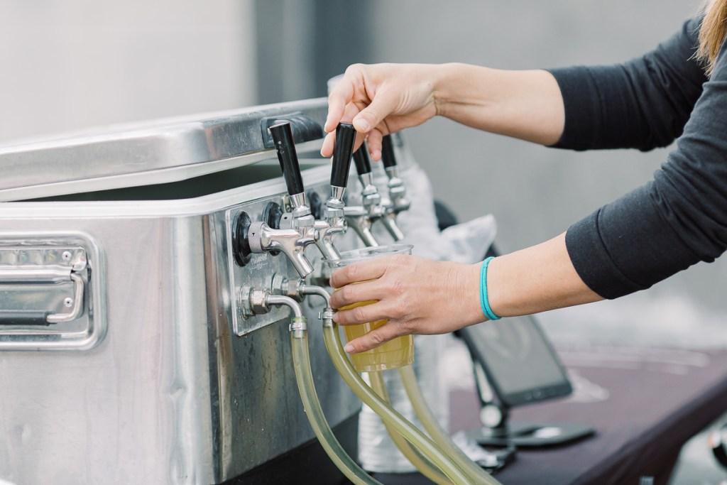Server pours beer during Innovation & Cinema event.