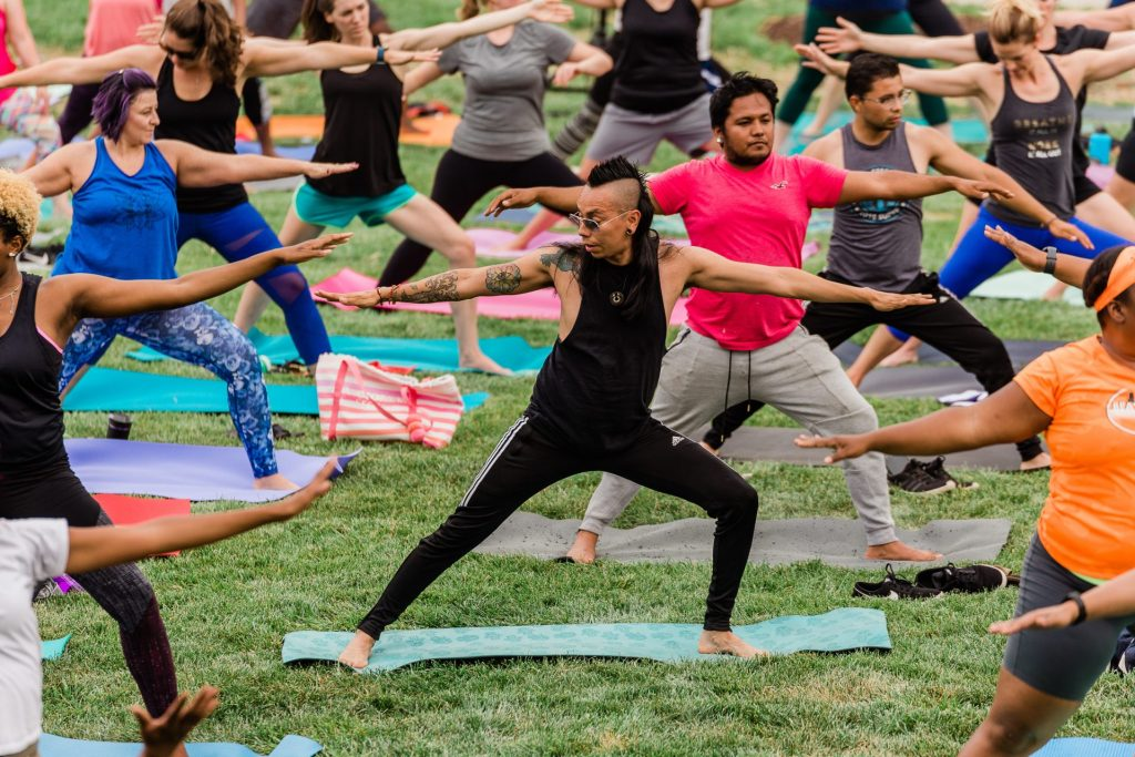 People practice yoga during Sunset Salutations community event.