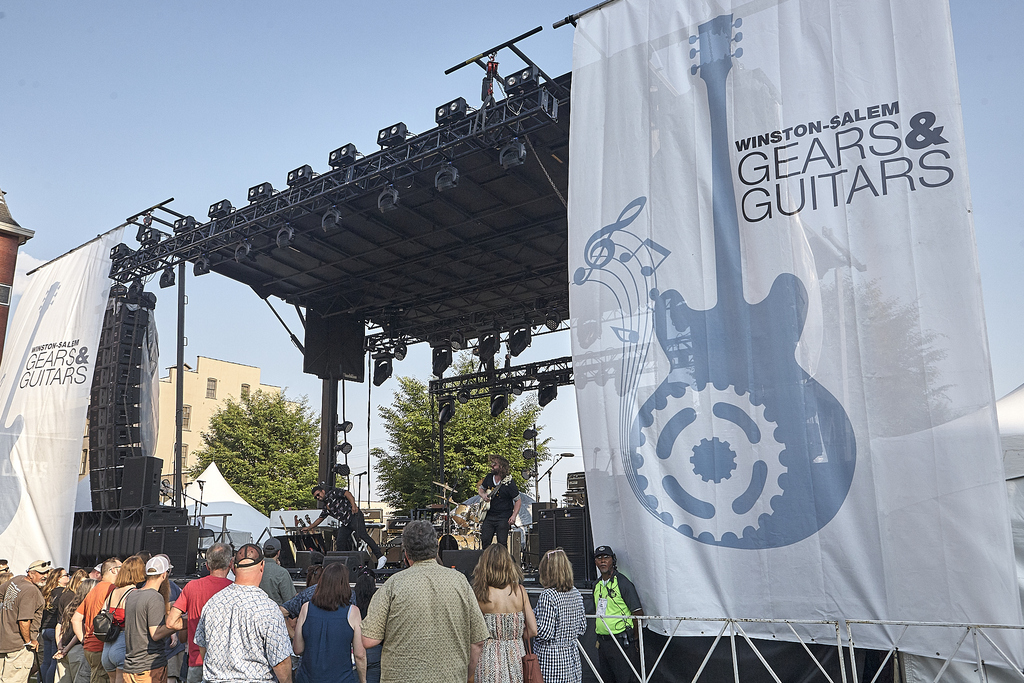 2019 Gears & Guitar Festival stage with banners and crowd.