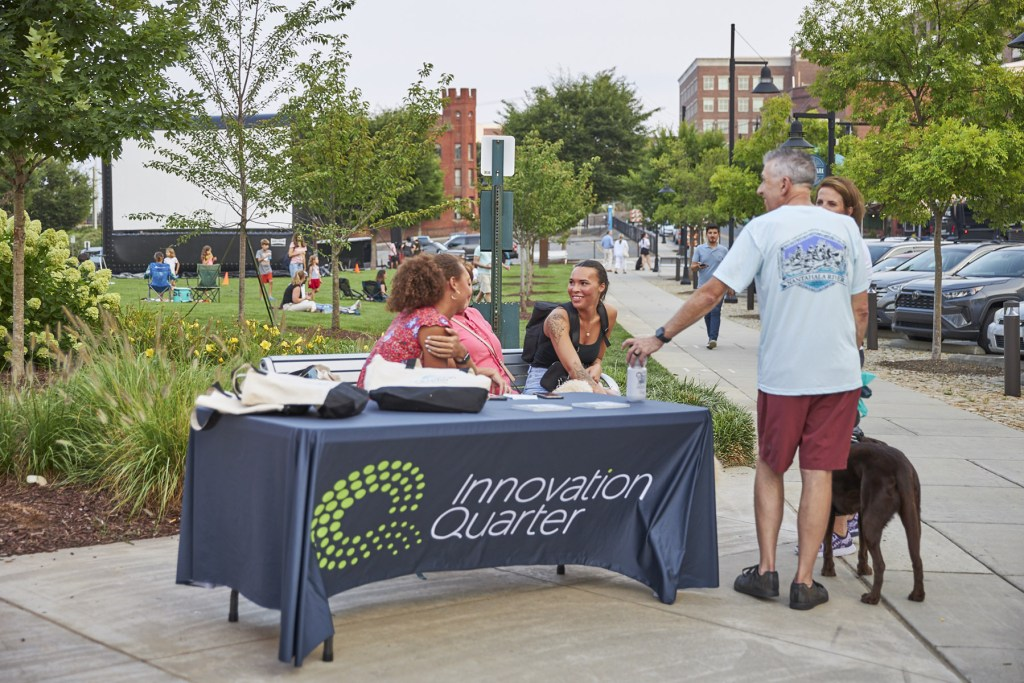 Innovation Quarter volunteers checking in people for an outdoor event.