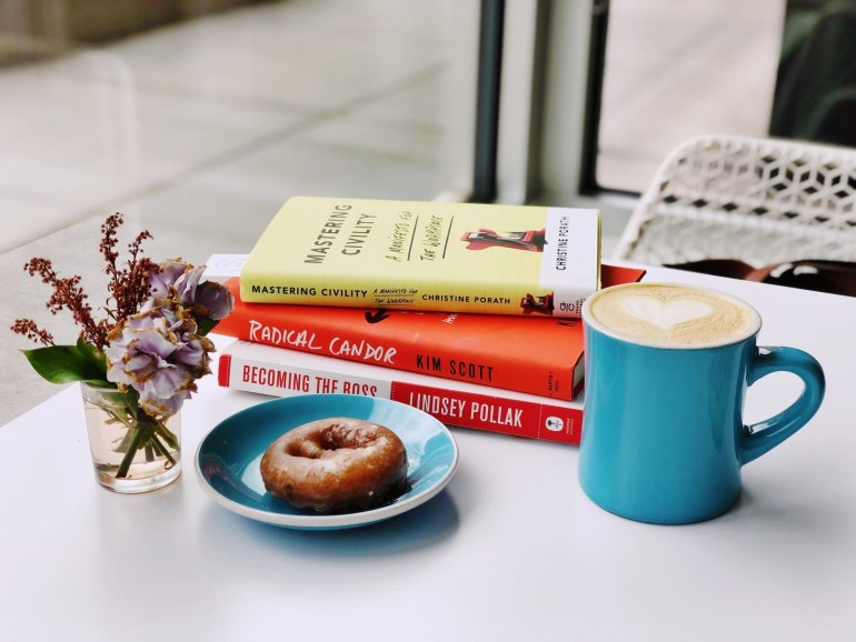 three books stacked on top of each other with coffee, a doughnut and flowers nearby