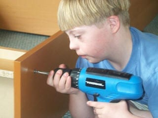 Boy with Down Syndrome using cordless drill to assemble a book case. (Photo credit: Wikipedia)
