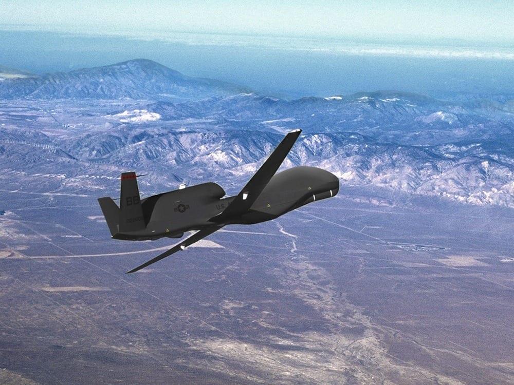An RQ-4 Global Hawk drone flies over mountains and desert. Credit: Northrop Grumman