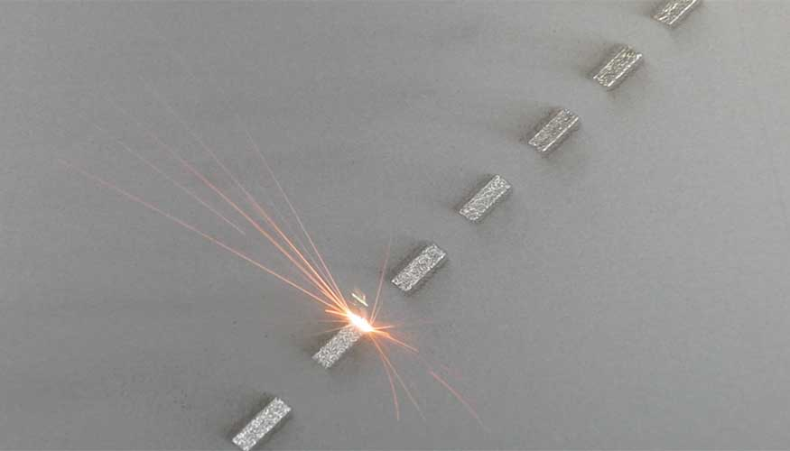 Direct metal laser melting (DMLM) machine in action: A laser fuses metal powder to form one of many successive layers that will form the final manufactured part.