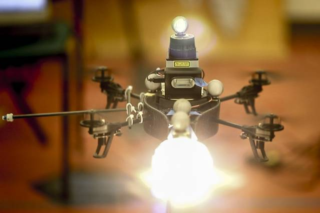 In the researchers' experiments, the robot helicopter was equipped with a continuous-light source, a photographic flash, and a laser rangefinder. Courtesy of the researchers