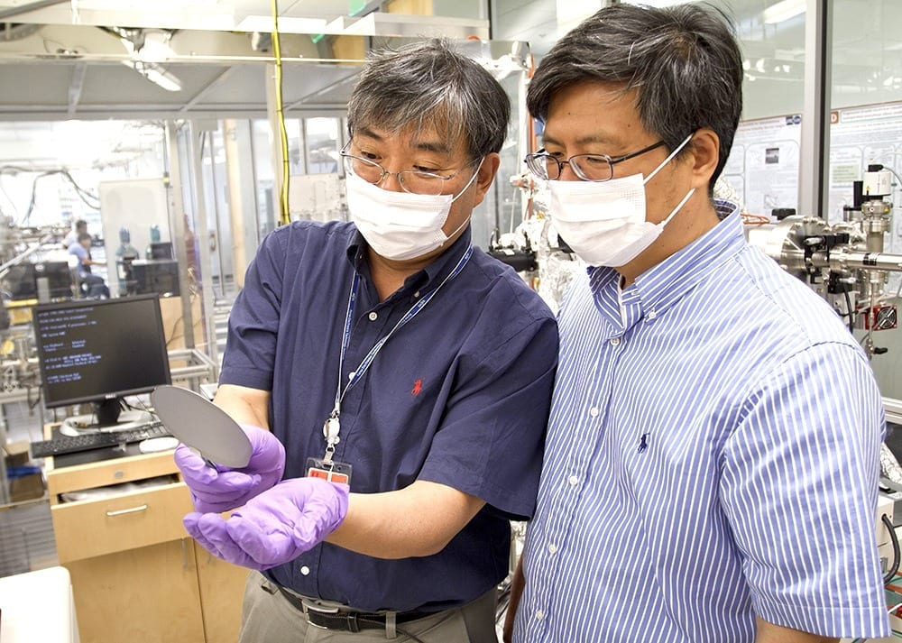 """Dr. Jiyoung Kim (left) and Dr. Kyeongjae """"K.J."""" Cho examine a wafer used to make transistors. The two created new technology that could reduce energy consumption in mobile devices and computers."""