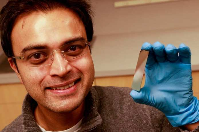 University of Utah electrical and computer engineering associate professor, Rajesh Menon, holds up a piece of silicon that has been etched with microscopic pillars and holes to create a polarized filter. He leads a team of researchers that have developed a new polarizer that can allow more light to pass through than conventional polarizers. This could lead to LCD displays for smartphones and tablets that last longer on a battery charge and cameras that can take better pictures at low light. Photo Credit: Dan Hixson/University of Utah College of Engineering
