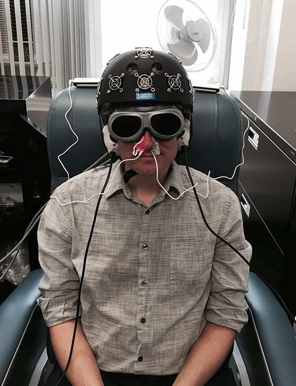 A staffer in Dr. Margaret Naeser's lab demonstrates the equipment built especially for the research: an LED helmet (Photomedex), intranasal diodes (Vielight), and LED cluster heads placed on the ears (MedX Health). The real and sham devices look identical. Goggles are worn to block out the red light. The near-infrared light is beyond the visible spectrum and cannot be seen. (Photo courtesy of Naeser lab)
