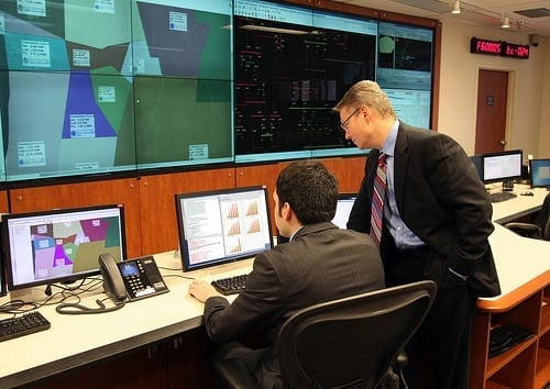 PNNL's Power Grid Integrator has demonstrated up to a 50 percent improvement in forecasting future electricity needs over several commonly used tools. Project lead Luke Gosink, right, consults on the use of the new tool, which could save millions in wasted electricity costs.