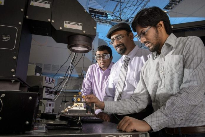 """Doctoral student Aditya G. Baradwaj (at left), professor Muhammad A. Alam (center) and doctoral student Ryyan Khan, operate a solar simulator. They are members of a research team led by former doctoral student Biswajit Ray and also involving assistant professor Bryan Boudouris. The group is reporting new findings that contradict a fundamental assumption about the functioning of """"organic"""" solar cells made of low-cost plastics. The findings suggest a new strategy for creating inexpensive solar technology. (Purdue University image/John Underwood)"""