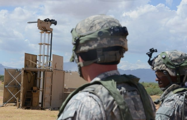 Lt. Col. Raphael Heflin, right, commander, 142nd Combat Service Support Battalion, 1st Armored Division, and another Soldier pass near a remotely-controlled weapons system, which has drastically reduced the number of Soldiers needed for perimeter...