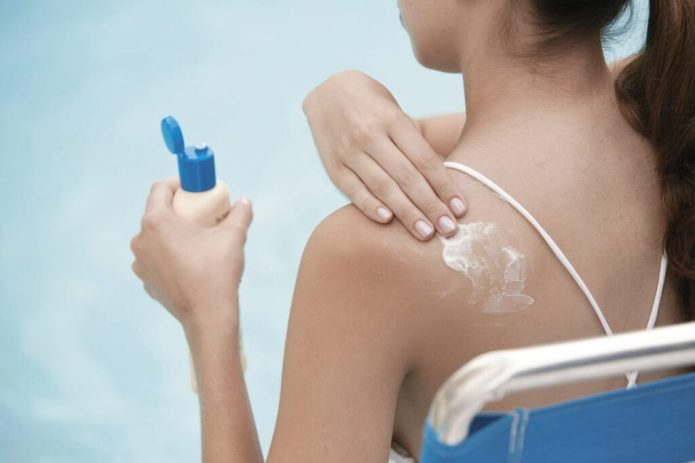Woman Applying Sunscreen --- Image by © Royalty-Free/Corbis