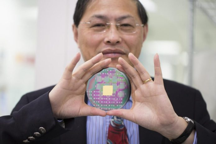 RMIT University's Professor Min Gu with the breakthrough nanophotonic chip that can harness the angular momentum of light. CREDIT RMIT University