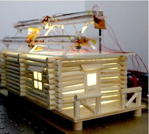 Hybrid solar and wind harvesting cells on the top of this model house collect enough energy to light it up inside. Credit: American Chemical Society
