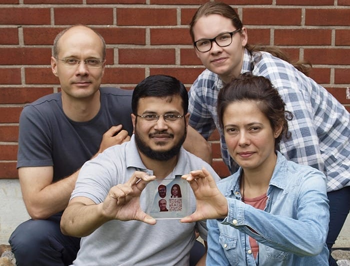 A semi-transparent dye-sensitized solar cell with inkjet-printed photovoltaic portraits of the Aalto researchers (Ghufran Hashmi, Merve Özkan, Janne Halme) and a QR code that links to the original research paper.