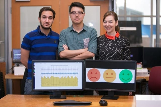 Left to right: PhD student Fadel Adib, PhD student Mingmin Zhao, and Professor Dina Katabi pose with their EQ-Radio device, which can detect emotion using wireless signals. Photo: Jason Dorfman/MIT CSAIL