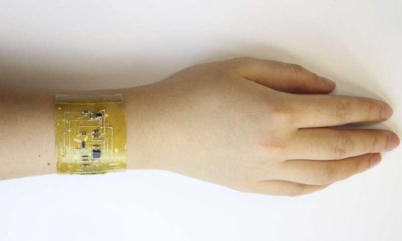 "A user fits an""electronic skin"" device onto the wrist. (Credit: Chuanqian Shi)"