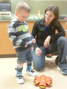 Child in his new orthotics with his physical therapist