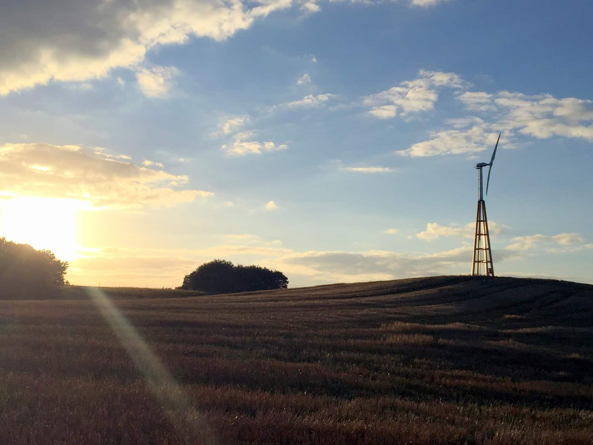 Dalifant small wind turbine 11 kW on a wooden tower installed on a farm field at sunset