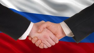 Photo of hands, two businessman handshaking in front of Russian flag