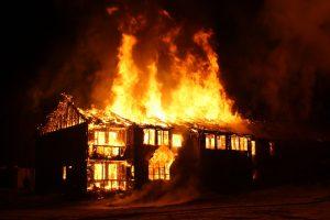 A house burning, presumably from negligence