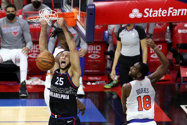 Ben Simmons, left, of the SIxers dunks between Nerlens Noel, in back, and Alec Burks, right,  of the Knicks during the 4th quarter of a NBA game at the Wells Fargo Center on March 16, 2021.