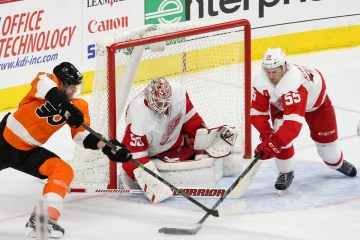 Defenseman Niklas Kronwall (#55) of the Detroit Red Wings swats the puck away from Right Wing Jakub Voracek (#93) of the Philadelphia Flyers