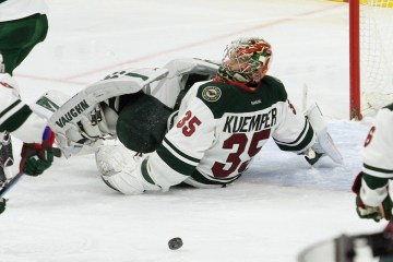 Goalie Darcy Kuemper (#35) of the Minnesota Wild rolls on his back to stop the puck