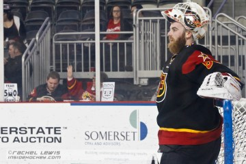 "Shane Owen (IND - 50) relaxes during a stoppage in play.  Indy fans place a ""Fear the Beard 50"" sign on the glass."