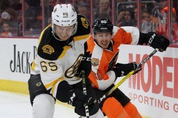 Defenseman Chris Casto (#65) of the Boston Bruins is pursued by Center Roman Lyubimov (#60) of the Philadelphia Flyers during the first period of the game between the Boston Bruins and the Philadelphia Flyers at the Wells Fargo Center. The visiting Boston Bruins defeated the Philadelphia Flyers by a score of 4-3 in a shootout.