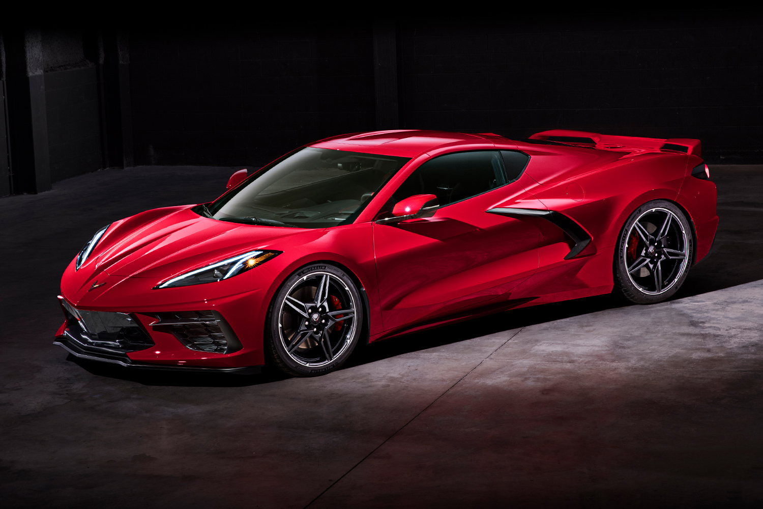 The 2020 Chevrolet Corvette Stingray, the eighth-generation version of the sports car painted red and sitting still against a black background