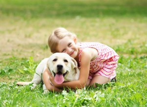 Little girl hugging a dog.