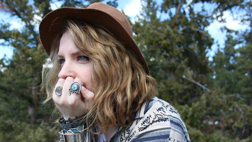 Blonde woman wearing brown hat looking left, thinking. She has rings on her second and fourth fingers. Trees are behind her.