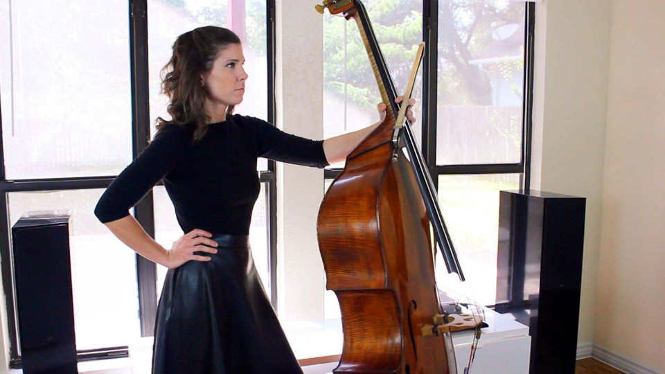 Bassist Lauren Pierce wears a black dress with her right hand on her hip. She is holding her bass and her bow with her left hand and look towards her left. There is a big window in the background.