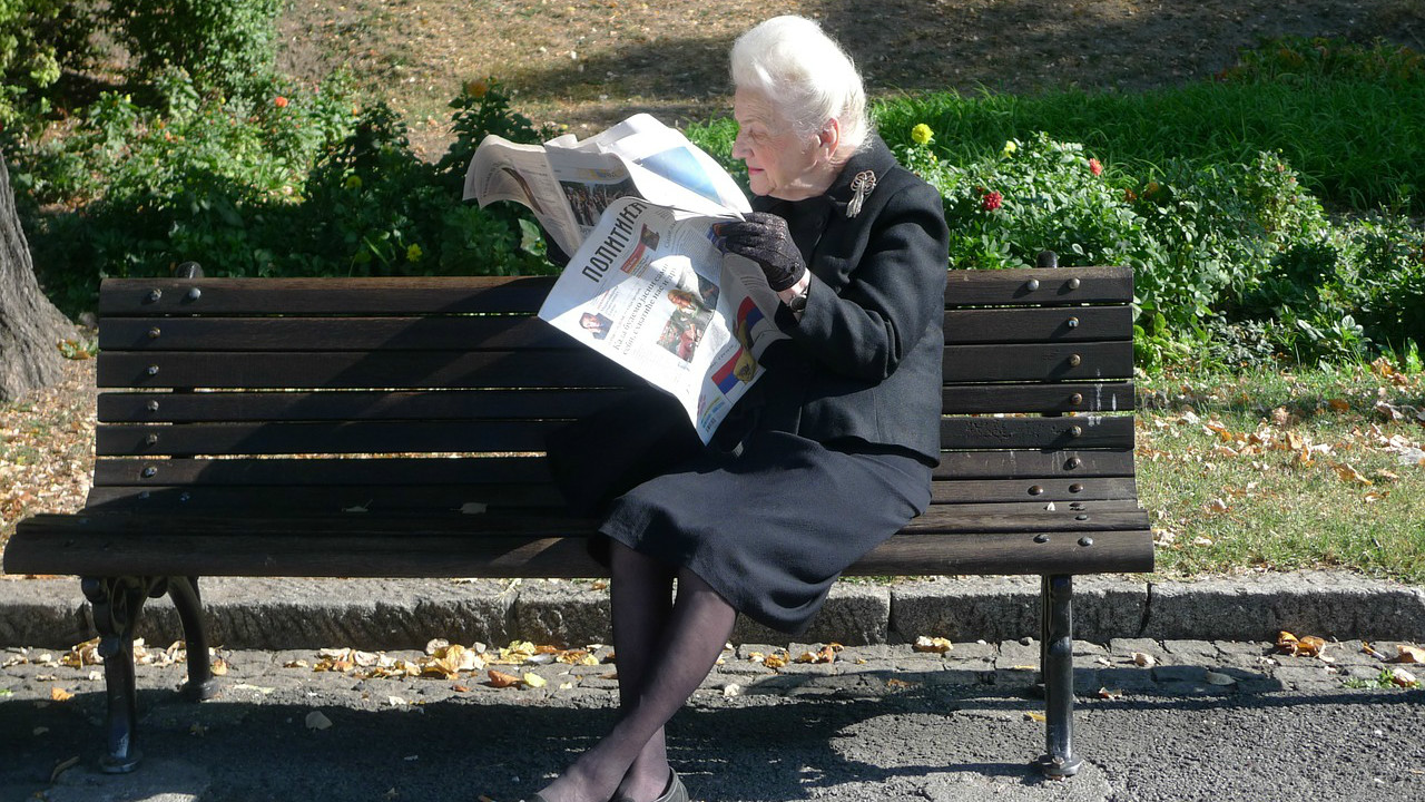 Elderly woman reading newspaper on a park bench. Her legs are crossed at her ankles, and she is facing to her right. She is wearing all black clothes, black gloves, and has white hair. Green grass, a couple yellow flowers, and green shrubs are behind her. The bench is dark brown wood, and it sits on top of asphalt.