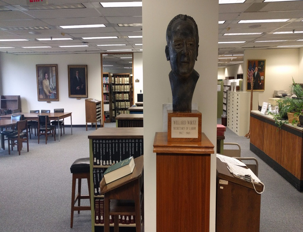 Photo from inside the Wirtz Labor Library. A bust of Secretary Willard Wirtz stands on a wooden pedastal in front of a white beam. On either side is a view of the stacks of the library.